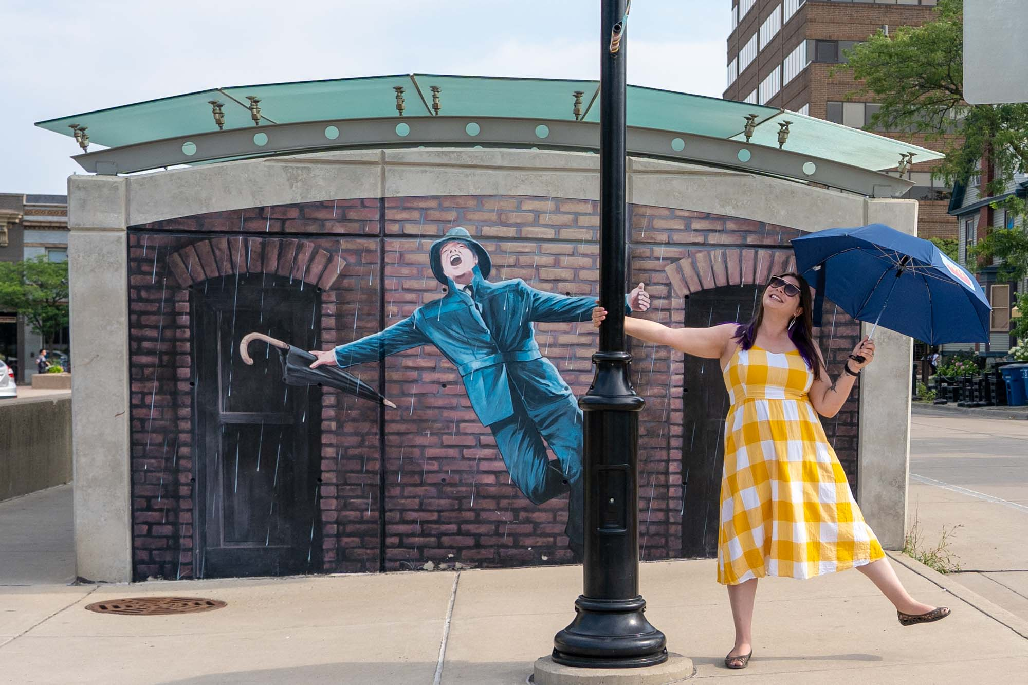 Girl with umbrella in front of the Singing in the Rain mural in Ann Arbor