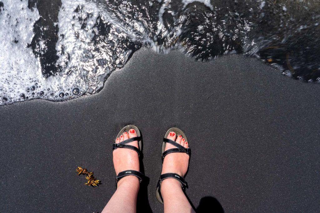 Feet on a black sand beach